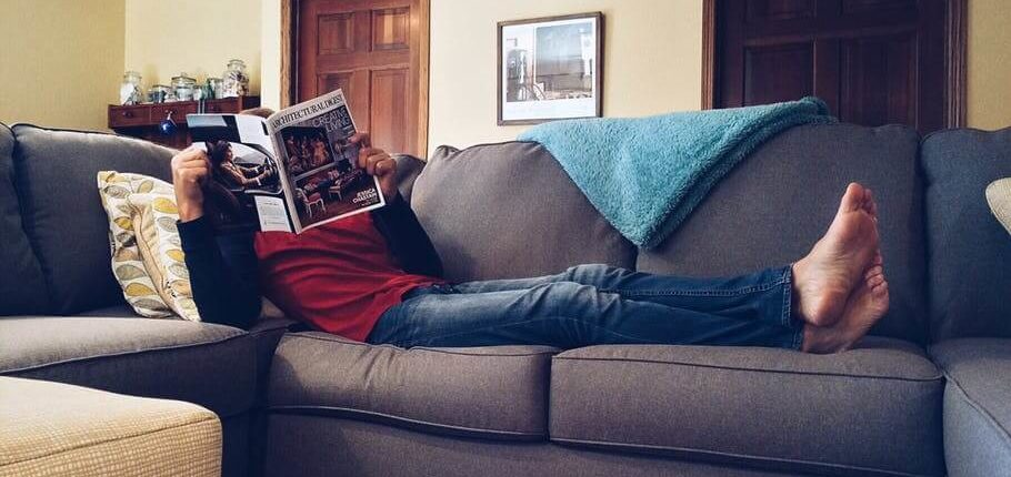 A man reclined on his sofa with a magazine
