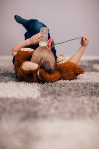 A child laying down on a carpet.