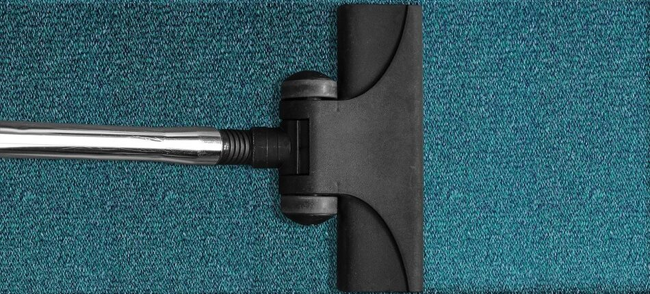 A closeup of a vacuum cleaner head cleaning a blue carpet.