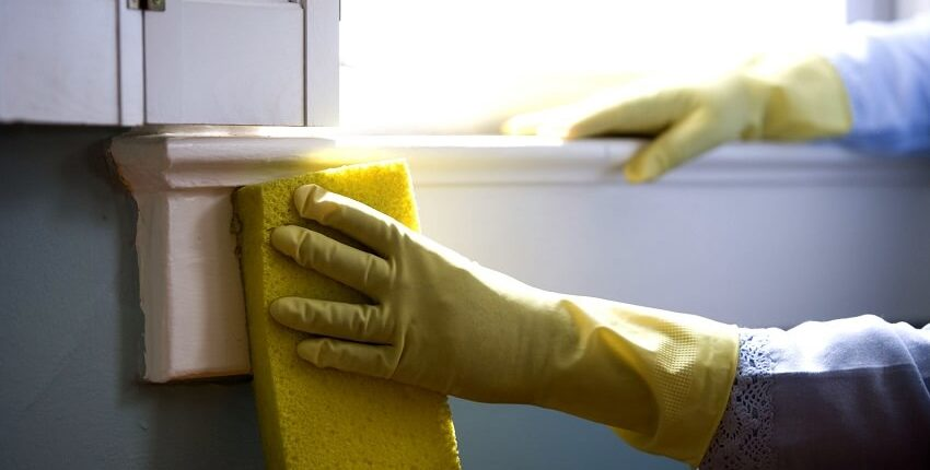 Yellow gloved hands washing a home's windows